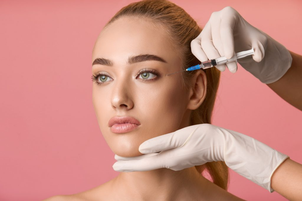 Young woman getting beauty injection near eyes