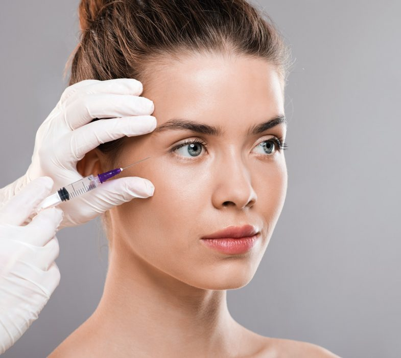 Attractive woman getting beauty injection, grey background