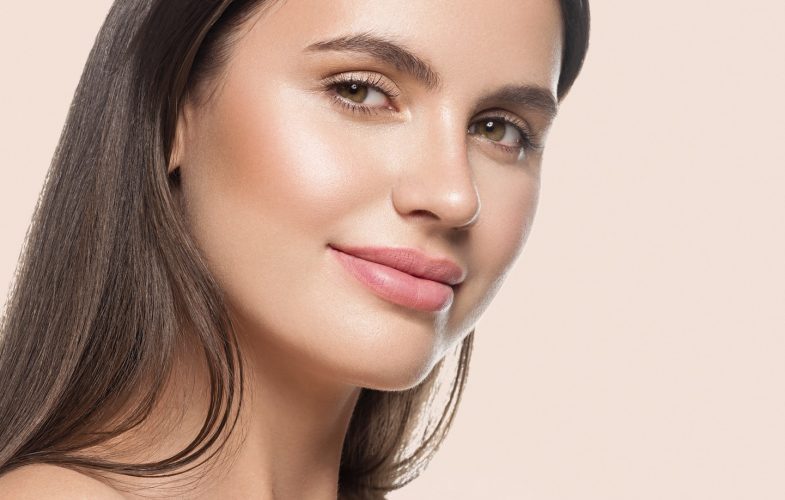 Woman beauty face healthy clean fresh skin natural makeup over pink