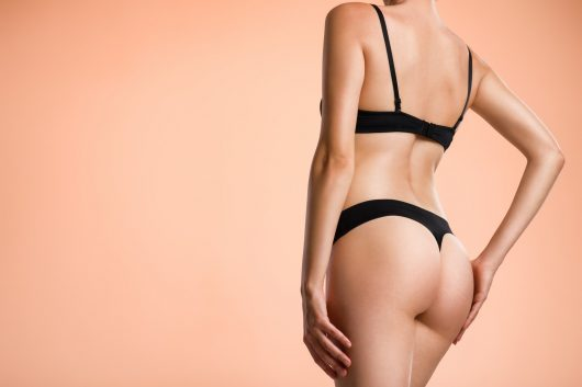 Young woman with beautiful buttocks. Rear view of a perfect female body.